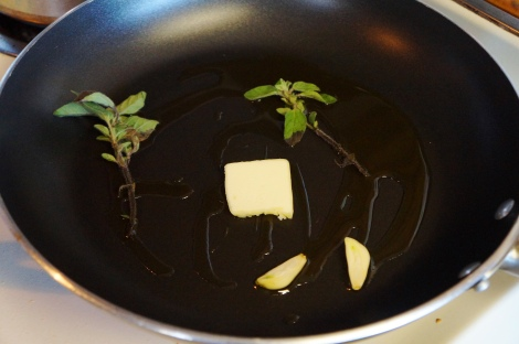 Olive oil and butter are flavored with fresh oregano and garlic